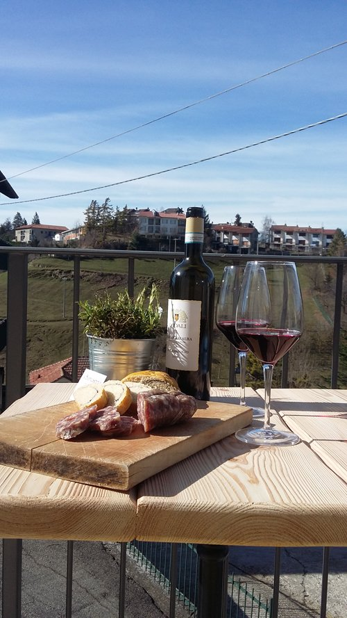 tagliere di affettati formaggi e calici di vino in terrazza