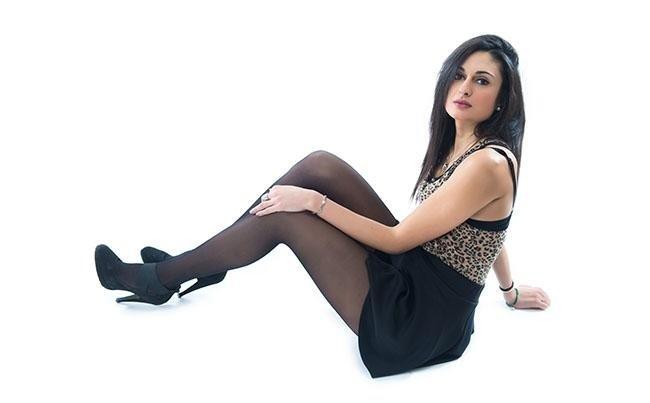 modella sdraiata con gambe in avanti indossa calze modello nero 40 denari new look