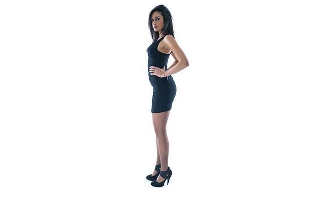 vista laterale modella con mani sulla vita indossa calze modello Nudo 40 denari castagna