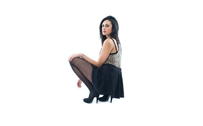 modella sdraiata indossa calze modello nero 40 denari new look