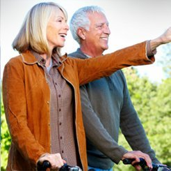Elderly couple bicycle riding outdoors