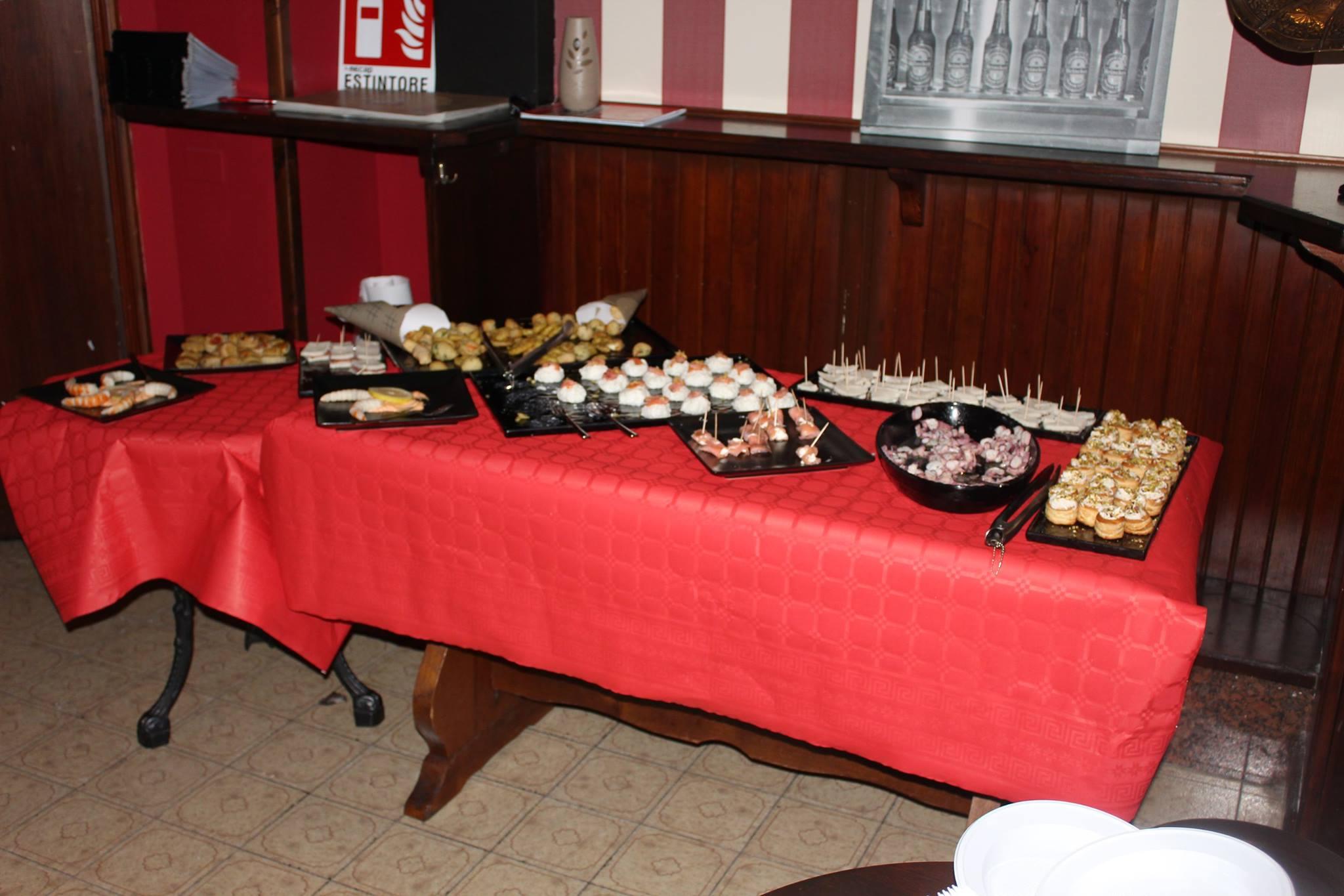 un tavolo con sopra anelli fritti,gamberi,tartine,tramezzini e altro