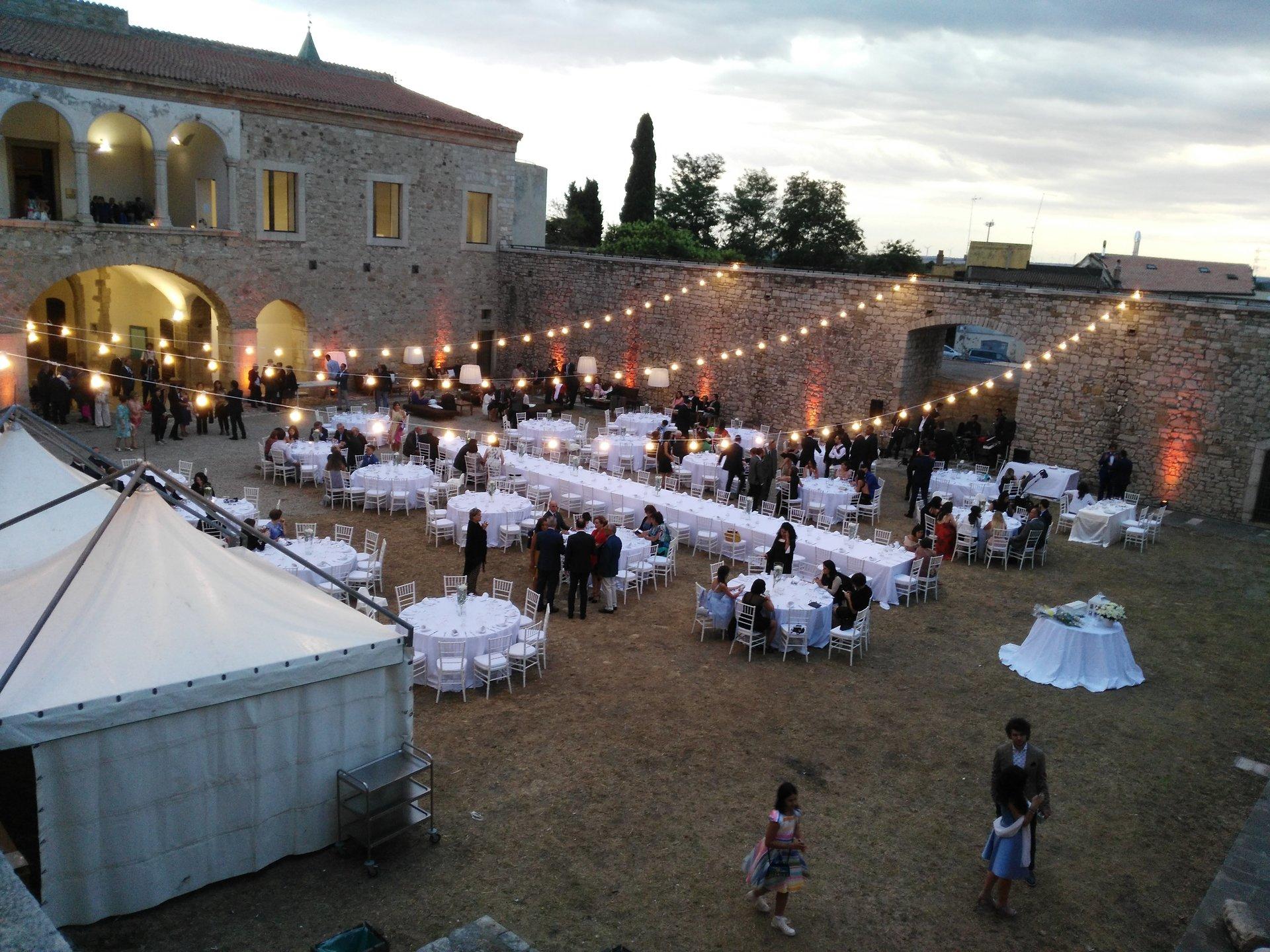 tavoli con vettovaglie bianche e luci a celebrazione di un matrimonio