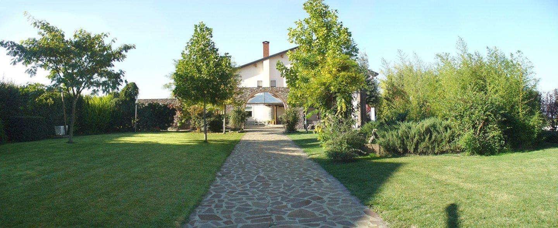 passerella in pietra in un giardino con una casa