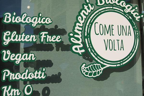 Una vetrina con scritto Come una volta Biologico, gluten free, vegan prodotti