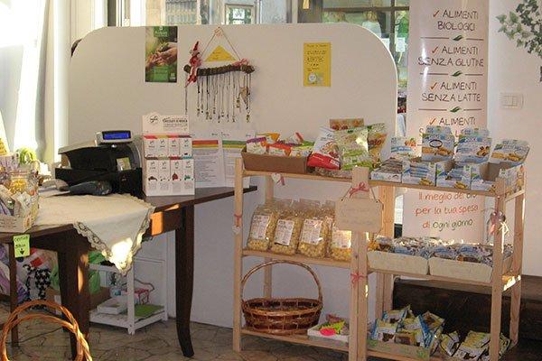 Due scaffali di legno con dei prodotti e un cartello con scritto Alimenti biologici