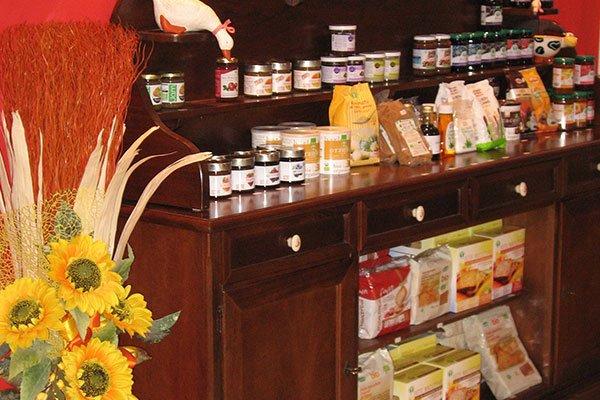 Un vaso con dei girasoli e accanto un mobile di legno con dei prodotti alimentari