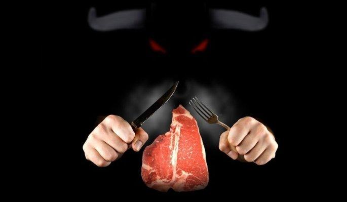 due mani con posate, una bistecca e una figura di toro
