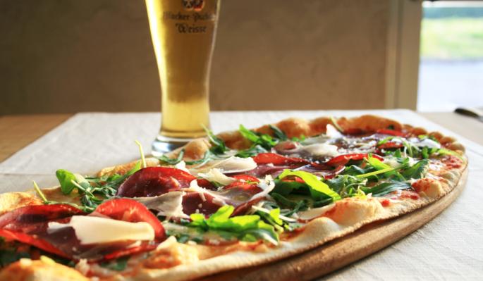 pizza ovale su un tagliere e un bicchiere di birra