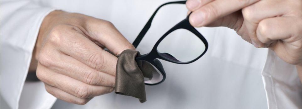 un ottico pulisce le lenti di un paio di occhiali