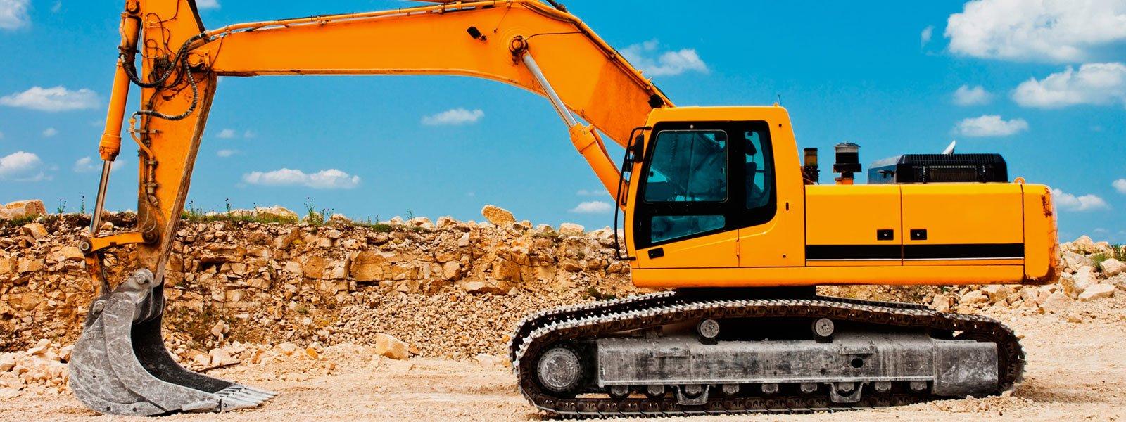 Primo piano di un escavatore gialla che contrasta con il cielo blu