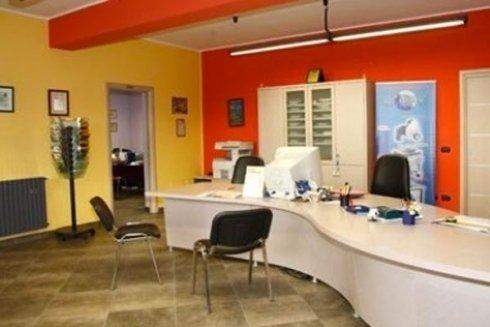 Vista interna di un ufficio moderno ammobiliato, con sedie nere, scrivanie bianche e muri di diverso colore