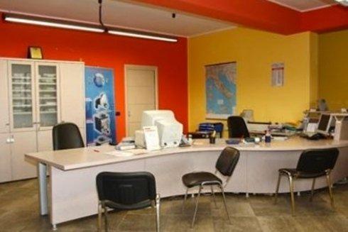 Vista di una scrivania d'ufficio, con sedie nere, pc bianco, e muri pitturati con colori giallo ed arancione