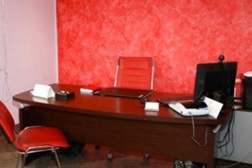Primo piano di una scrivania da ufficio in legno, con poltrone rosse e pc nero