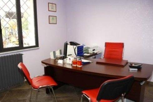 Vista interna di un ufficio molto luminoso con sedie rosse ed una scrivania in legno