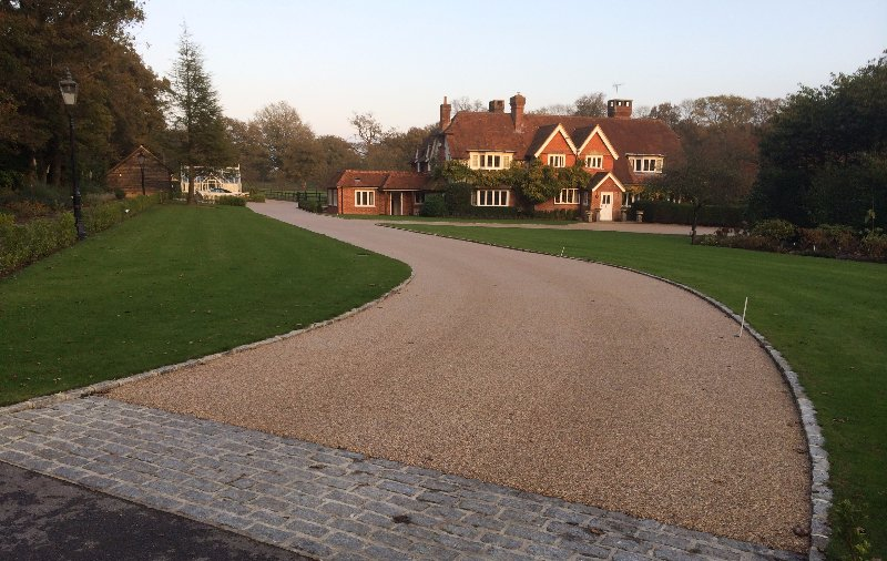 gravel drive with cobble setts, leading to large country home