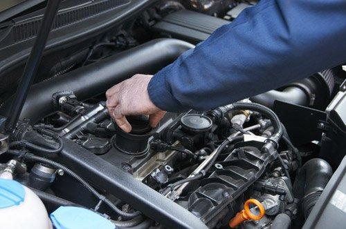 meccanico mentre sta controllando olio su motore di una macchina