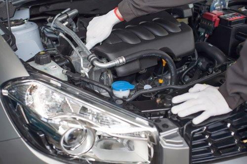 meccanico con guanti mentre lavora su motore di una macchina