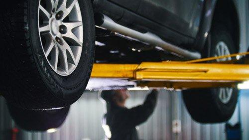 meccanico mentre lavora una sollevato auto
