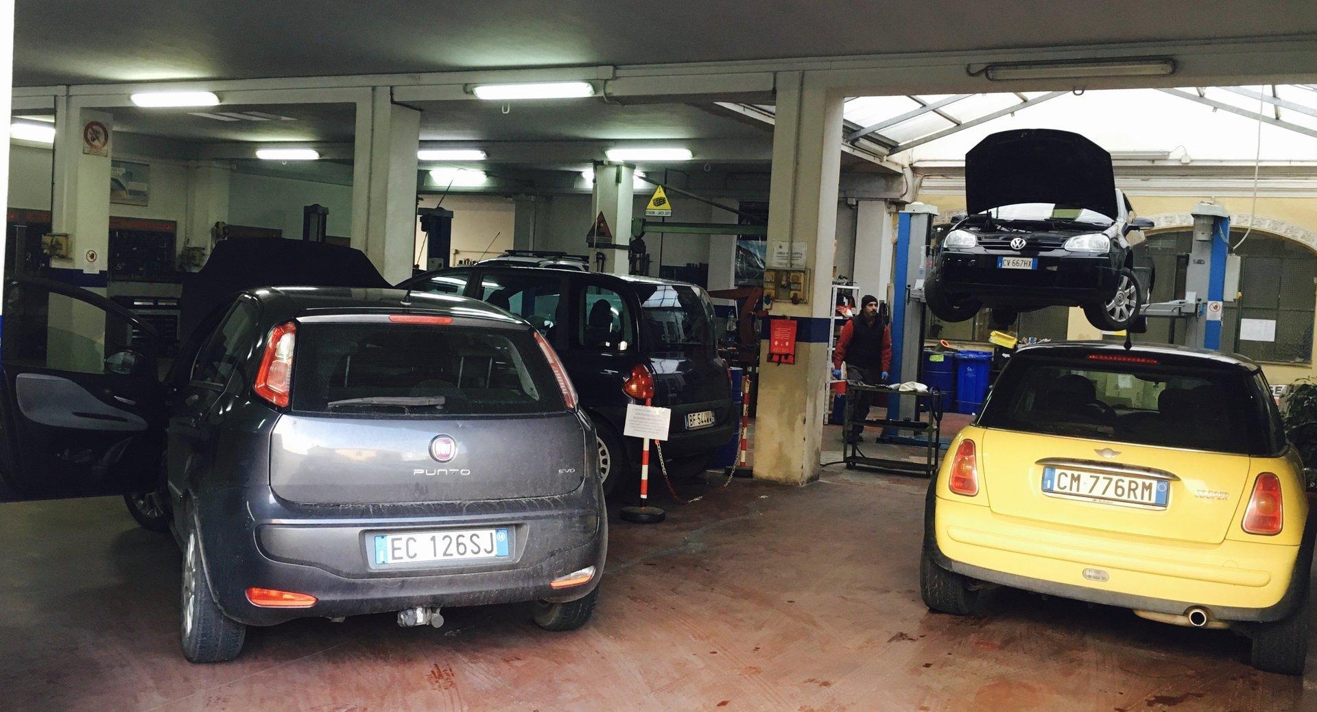 una macchina grigia ed una gialla in un'officina