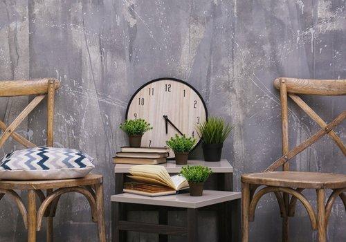 due sedie in legno con cuscino, orologio, vasi e libri sul scrivania
