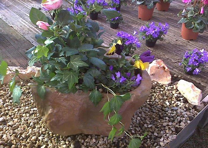 Fioriera in pietra con fiori