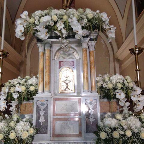 Chiesa decorata per nozze con ghirlande di le orchidee e rose bianche sull'altare e centri delle stesse fiori ai lati