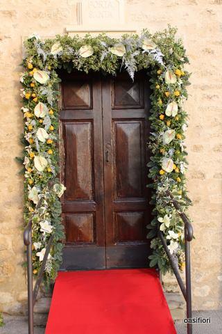 Decorazione floreale circondando la porta in colore verde con fiori gialle e bianche