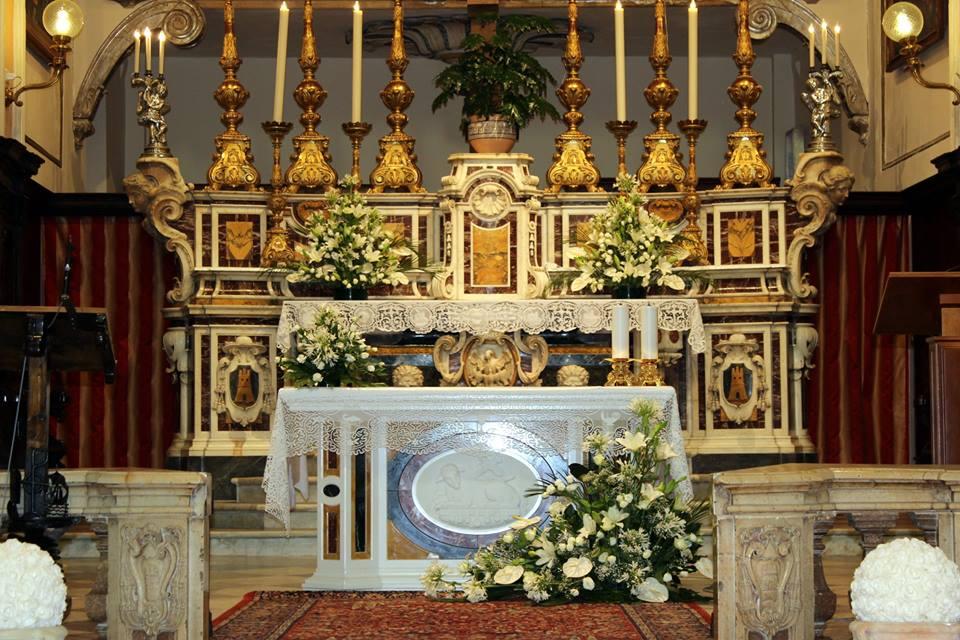 Altare decorato con composizioni floreali verdi e bianche