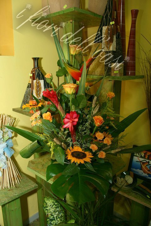 Centro floreale con fiori rosse del paraiso, rose gialle e girasoli