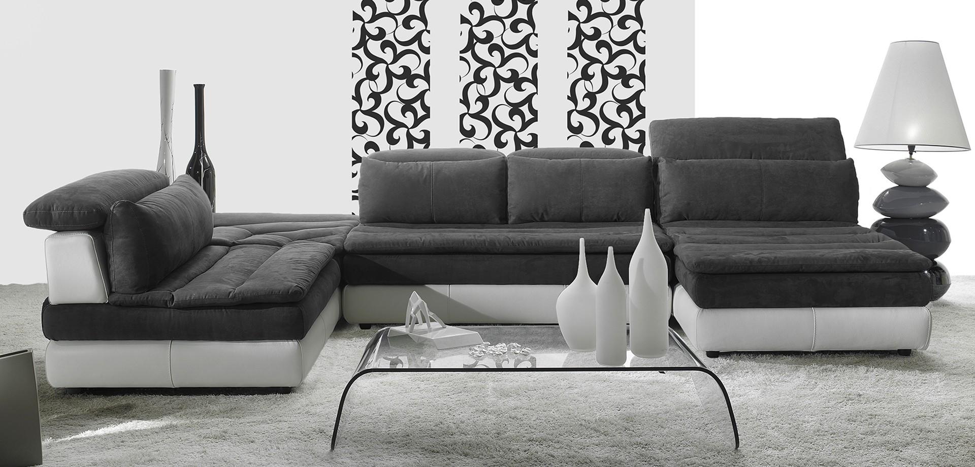 Una sala con due divani da due posti di color bianco, un tavolino di color nero e una lampada da tavolo di color nero