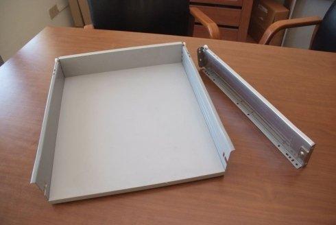 un cassetto di legno di color bianco e accanto una cerniera