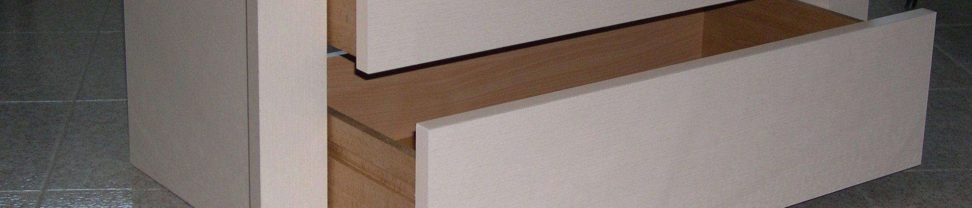 Un cassetto in legno di color bianco con una cerniera
