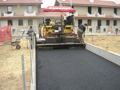 uomini al lavoro per asfaltare la strada