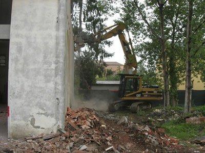 demolizione di un muro da parte di una ruspa scavatrice