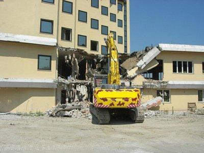 macchina durante la demolizione di un edificio