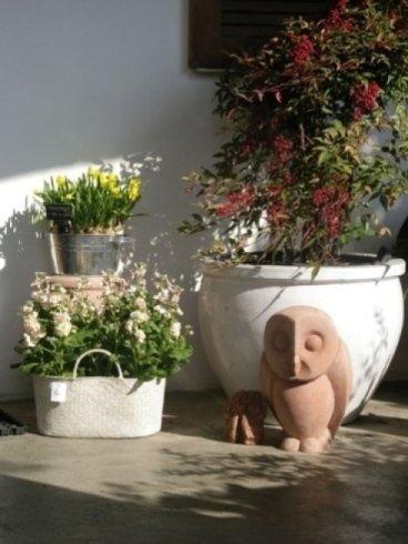 vasi bianchi, ornamenti in terracotta, gufi da giardino