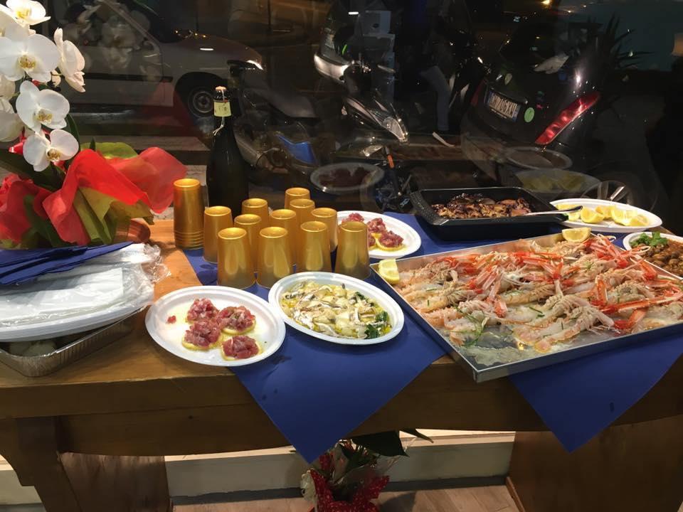 un tavolo con sopra dei piatti a base di pesce e dei bicchieri color oro