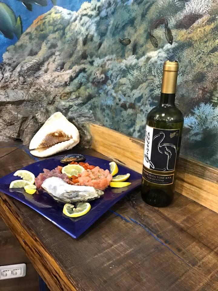 un piatto di pesce, una bottiglia di vino e dietro vista  di un acquario