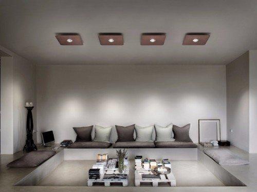 un salotto moderno con due tavolini e delle luci marroni quadrate sul soffitto