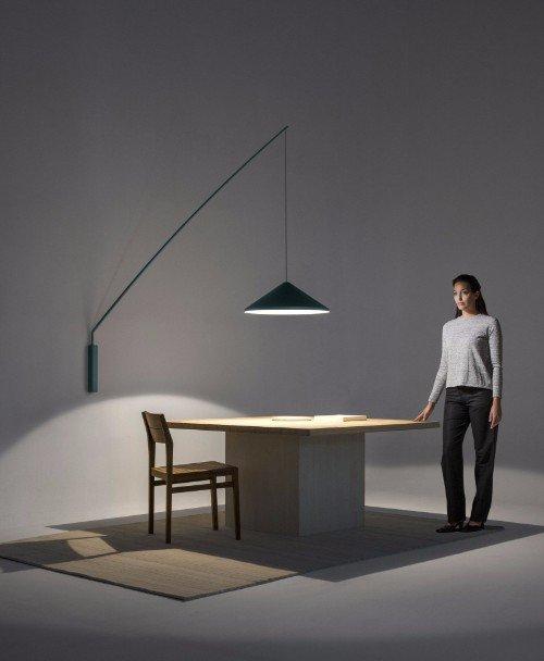 una donna vicino a una scrivania con una sedia e una lampada a muro di color blu