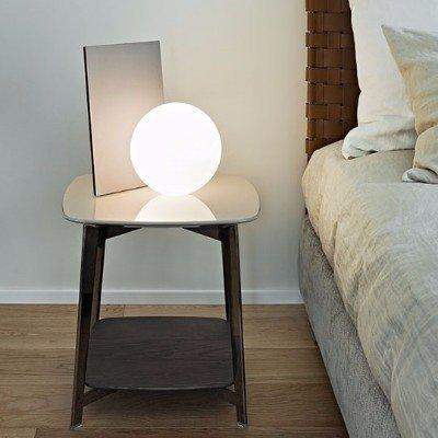 un comodino con sopra una lampada rotonda