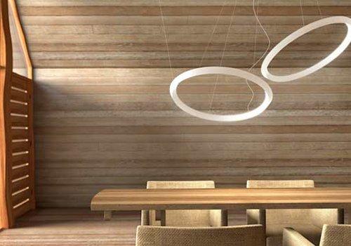 un tavolo di legno con delle sedie e due lampadari a forma circolare