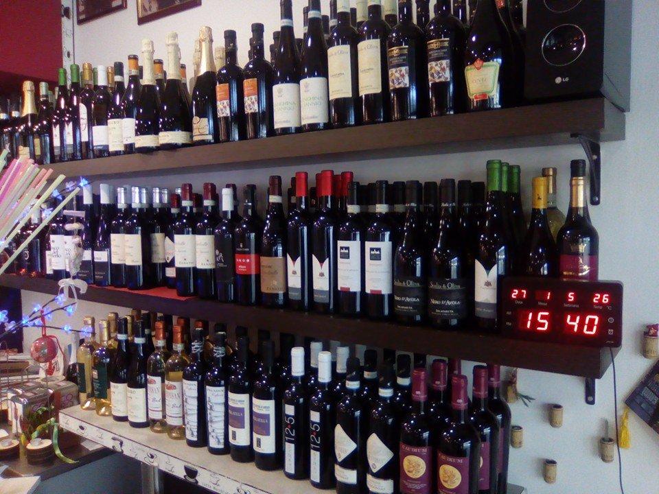 una serie di bottiglie di vino esposte su tre mensole una sopra l'altra