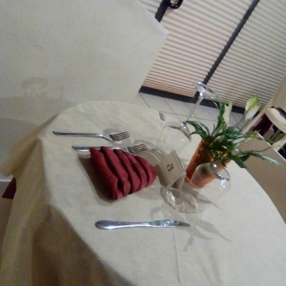 un tavolo apparecchiato con un tovagliolo bordeaux, posate,bicchieri e un vaso con una piantina