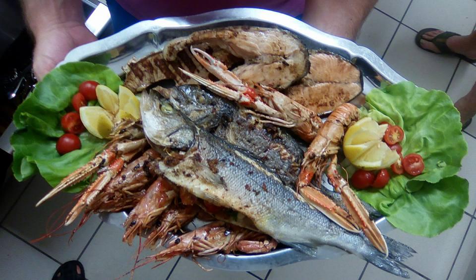 un piatto a base di pesce,gamberoni,insalata pomodorini e fette di limone