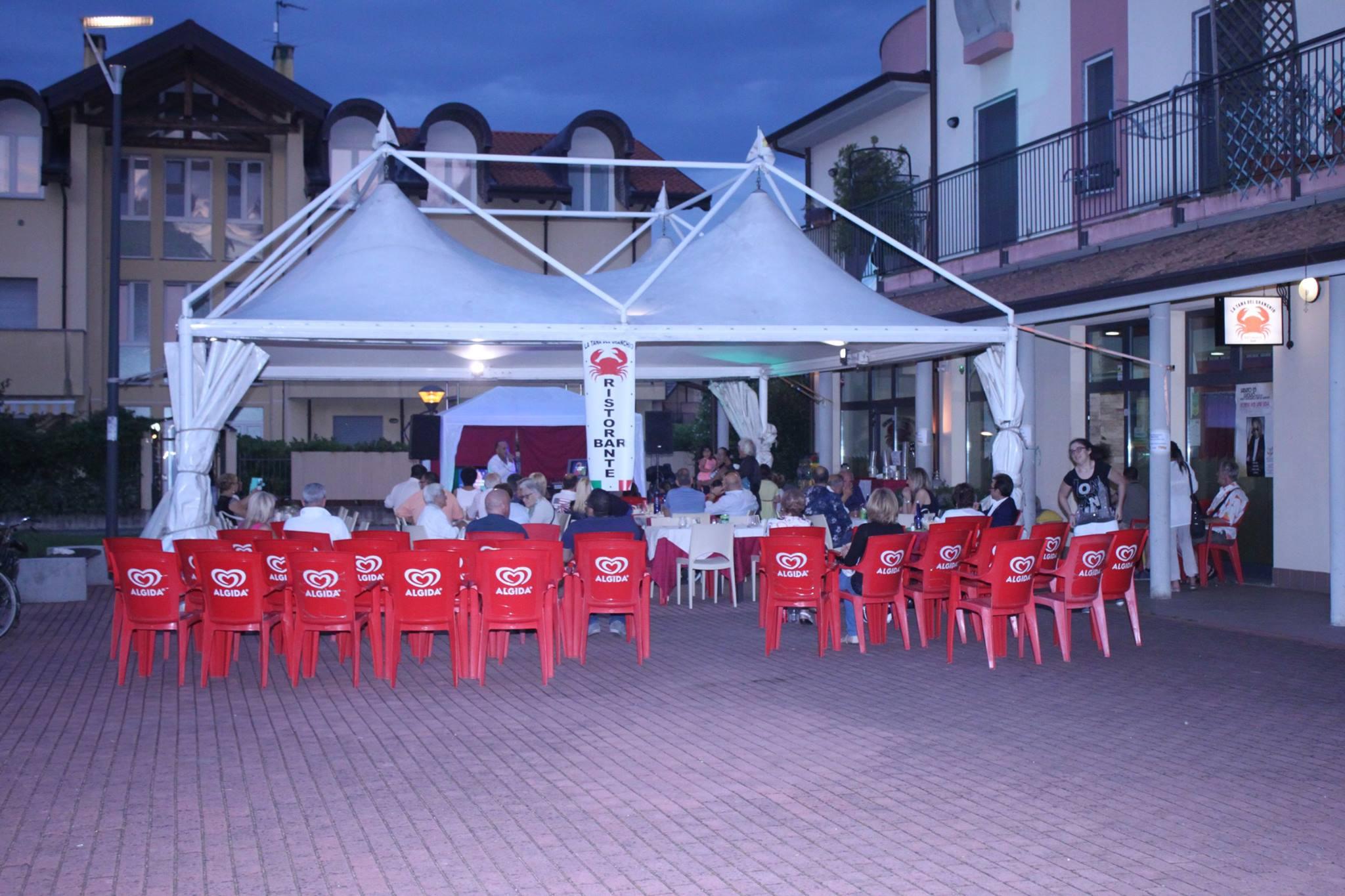 delle persone a tavola sotto un gazebo con un tendone bianco e delle sedie rosse