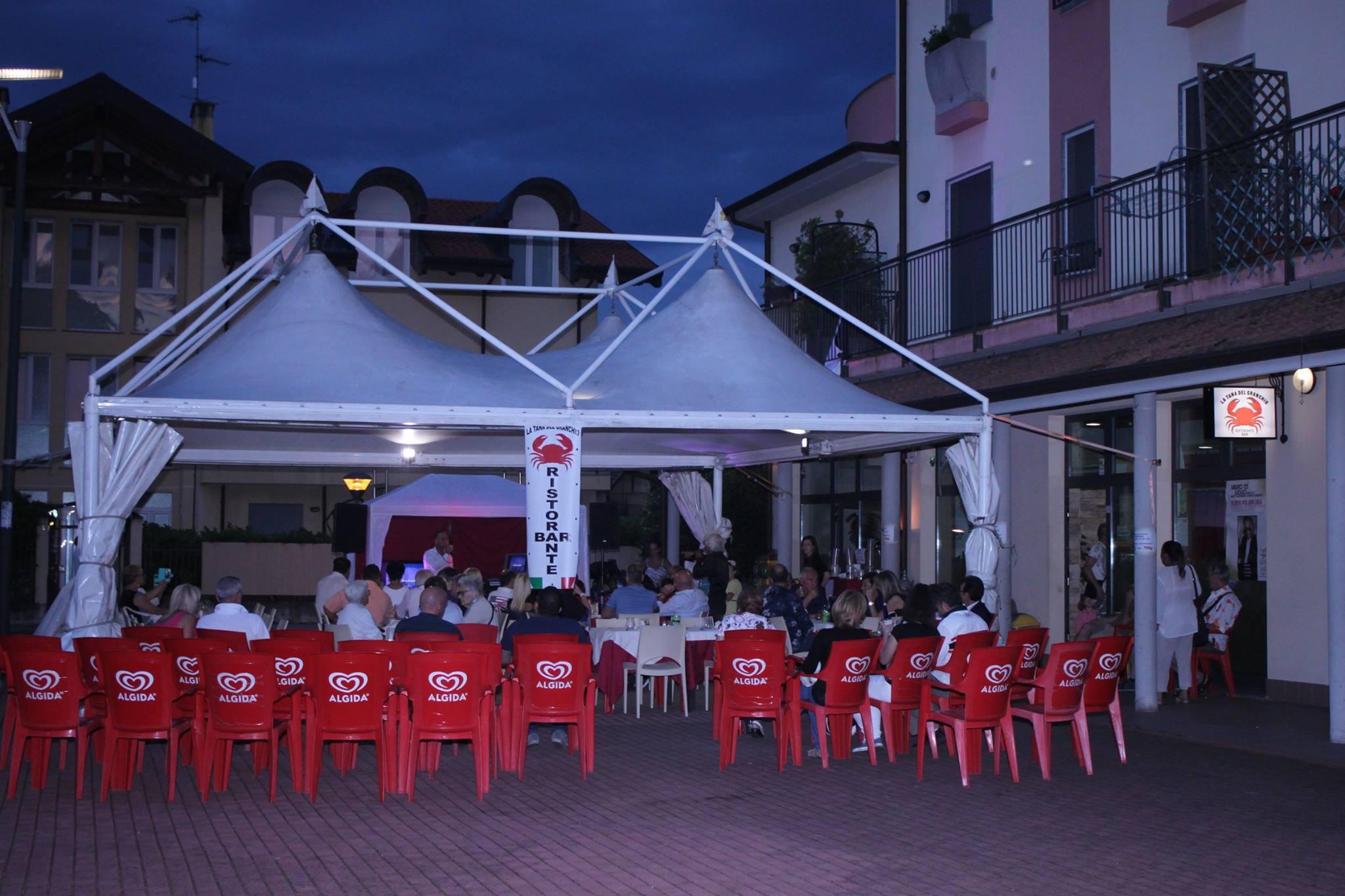 della gente a tavola sotto un gazebo con un tendone bianco e delle sedie rosse
