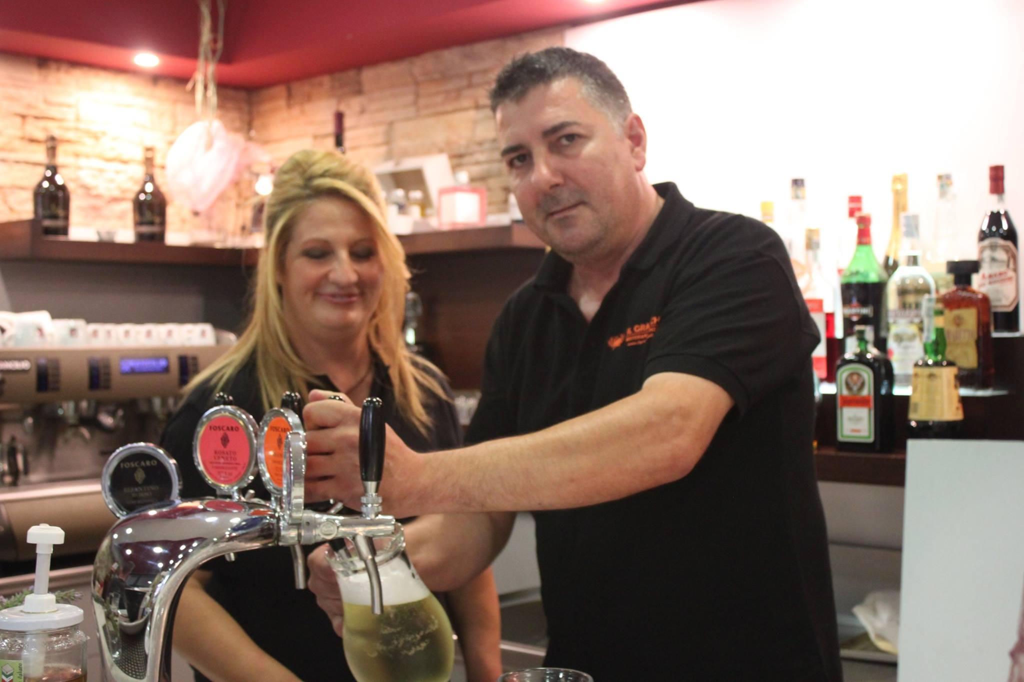 un uomo in posa per una foto mentre riempie un bicchiere di birra alla spina e accanto una donna bionda
