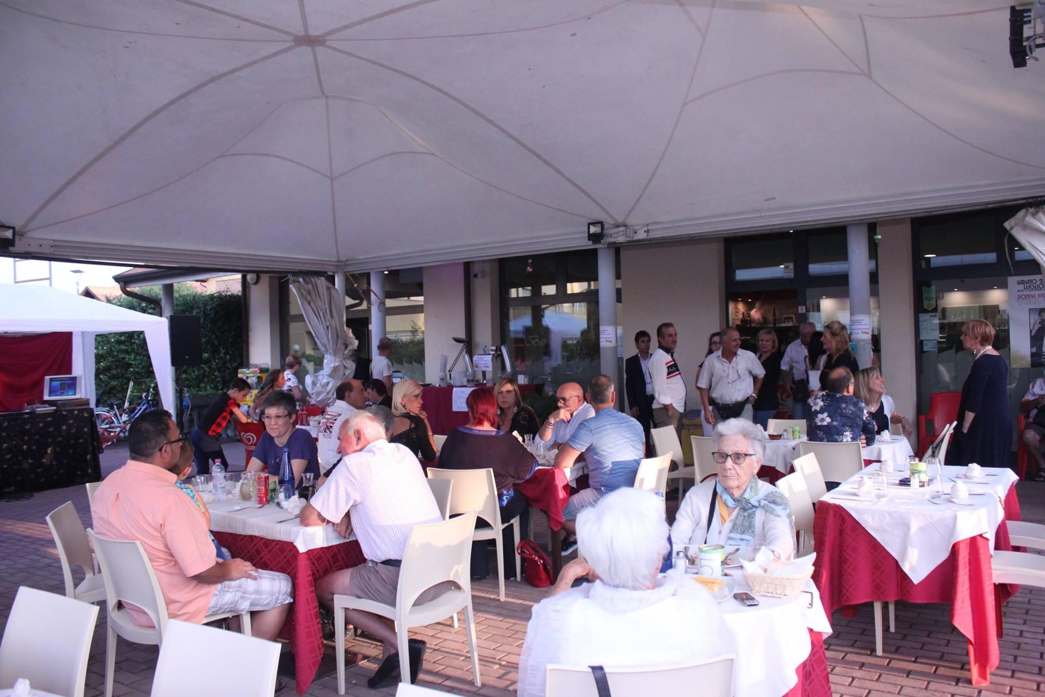 delle persone a tavola sotto un tendone bianco all'esterno del ristorante